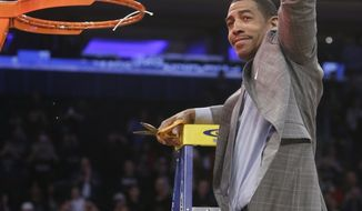 Connecticut head coach Kevin Ollie displays the net to the crowd after cutting it down after the regional final against Michigan State in the NCAA college basketball tournament  Sunday, March 30, 2014, in New York. Connecticut won 60-54. (AP Photo/Frank Franklin II)