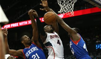 Atlanta Hawks forward Paul Millsap (4) attempts a shot as he is defended Philadelphia 76ers forward Thaddeus Young (21) and Philadelphia 76ers forward Jarvis Varnado (40) in the first half of an NBA basketball game Monday, March 31, 2014, in Atlanta. (AP Photo/Jason Getz)
