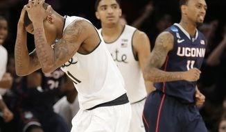 Michigan State's Keith Appling, left, reacts after loosing to Connecticut 60-54 in a regional final at the NCAA college basketball tournament, Sunday, March 30, 2014, in New York. Michigan State's Gary Harris, center, and Connecticut's Ryan Boatright were nearby. (AP Photo/Seth Wenig)