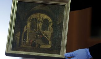 A woman lifts the painting 'Palace Stairs' by 18th-century Venetian artist Francesco Guardi during a hand over ceremony at the Foreign Ministry in Berlin, Germany, Monday, March 31, 2014. The painting was taken from Poland's National Museum in 1939 and after World War II, it passed into the collection of the State Gallery of Baden-Wuerttemberg. It was given back by German Foreign Minister Frank-Walter Steinmeier to his counterpart from Poland, Radoslaw Sikorski on Monday. (AP Photo/Michael Sohn)