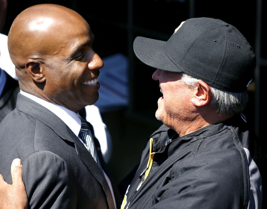 Former Pittsburgh Pirates outfielder Barry Bonds, left is greeted by current manager Clint Hurdle during opening day ceremonies before the baseball game between the Pittsburgh Pirates and the Chicago Cubs on Monday, March 31, 2014, in Pittsburgh.  (AP Photo/Keith Srakocic)