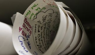 In this March 26, 2014 photo, a placard featuring hand-written messages of condolence and support, that was part of memorial to bombing victims near the finish of the 2013 Boston Marathon, rests on a shelf at the city archives in Boston. Thousands of items from the original memorial are going on display at the Boston Public Library in April 2014 to mark the anniversary of the attacks. (AP Photo/Steven Senne)