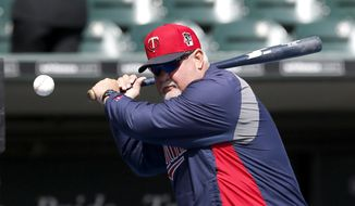 Minnesota Twins manager Ron Gardenhire hits infield practice before an opening day baseball game against the Chicago White Sox Monday, March 31, 2014, in Chicago. (AP Photo/Charles Rex Arbogast)