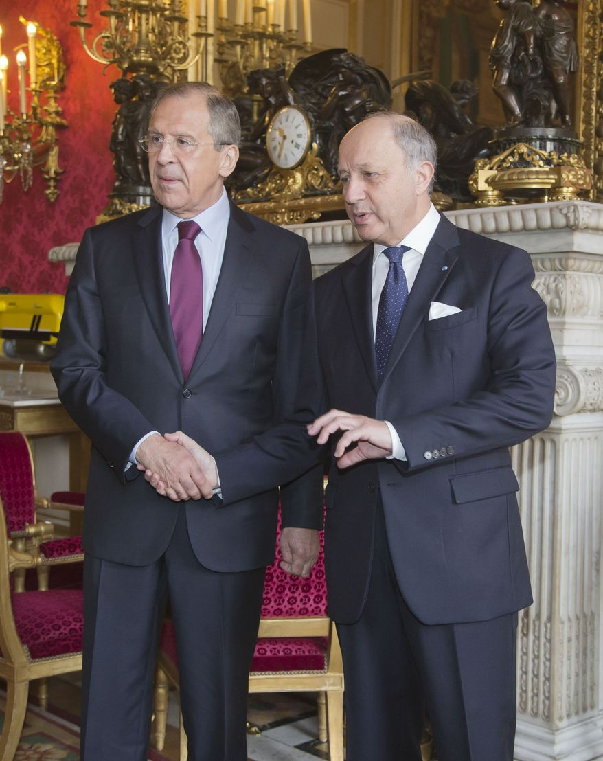 Russian Foreign Minister Sergey Lavrov, left, and French Foreign Minister Laurent Fabius, right, shake hands in the lobby of the foreign ministry in Paris, Monday, March 31, 2014. Lavrov is in Paris for talks about Ukraine.  (AP Photo/Michel Euler)