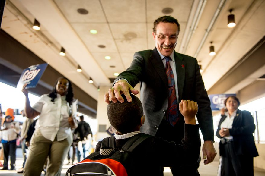 Washington, D.C. Mayor Vincent Gray greets Antonio Posey, 5, as he greets District residents at the Rhode Island Metro Station the night before election day, Washington, D.C., Monday, March 31, 2014. (Andrew Harnik/The Washington Times)