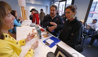 Michelle Decker, left, an employee of Connect For Health Colorado, the state's health care exchange, explains options and procedures to Virginia and Jose Sotelo, who signed up for insurance on the last day before fines are imposed, in Denver, Monday, March. 31, 2014. Colorado has already exceeded baseline federal goals for enrollment. As of last week, 106,000 Coloradans had signed up for private insurance since the exchange opened in October. Another 151,000 had enrolled in Medicaid. (AP Photo/Brennan Linsley)