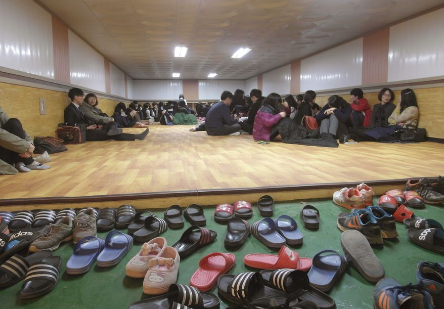 Residents and students of Yeonpyeong Island evacuate to a shelter on the island, South Korea, near the West Sea border with North Korea, Monday, March 31, 2014. North and South Korea fired artillery shells into each other's waters Monday, a flare-up of animosity between the rivals that forced residents of five front-line South Korean islands to evacuate to shelters, South Korean officials said. (AP Photo)