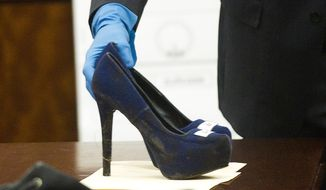 Prosecutor John Jordan sets down a stiletto shoe entered into evidence during the trial against Ana Lilia Trujillo Tuesday, April 1, 2014, in Houston. Trujillo, 45, is charged with murder, accused of killing her 59-year-old boyfriend, Alf Stefan Andersson with the heel of a stiletto shoe, at his Museum District high-rise condominium in June 2013. (AP Photo/Houston Chronicle, Brett Coomer) MANDATORY CREDIT