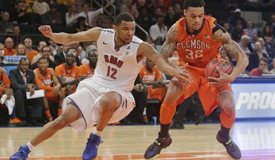 SMU's Nick Russell (12) and Clemson's K.J. McDaniels (32) fight for control of the ball during the first half of an NCAA college basketball game in the semifinals of the NIT Tuesday, April 1, 2014, in New York. (AP Photo/Frank Franklin II)
