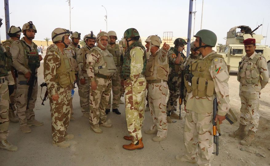 In this photo released by the Iraqi Army taken on March 20, 2014, the commander of Anbar Operations, Lt. Gen. Rasheed Fleih, center, speaks with officers before attacking al-Qaida positions in Ramadi, 70 miles (115 kilometers) west of Baghdad, Iraq. Iraqi military officials are warning that efforts to clear militants from Fallujah and parts of nearby Ramadi are proving much more difficult than they anticipated when the jihadists showed up three months ago. That realization, as they acknowledged during a recent tour of special forces operations, casts doubt on Iraq's ability to hold elections in Fallujah next month. (AP Photo/Iraqi Army)