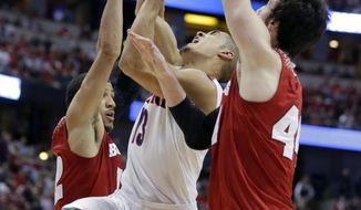 Arizona guard Nick Johnson, middle, drives past Wisconsin guard Traevon Jackson, left, and forward Frank Kaminsky during the first half in a regional final NCAA college basketball tournament game, Saturday, March 29, 2014, in Anaheim, Calif. (AP Photo/Alex Gallardo)