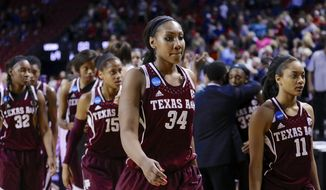 Texas A&M's Karla Gilbert (34), Texas Tori Scott (15), Curtyce Knox (11), Tavarsha Scott-Williams (32) walk off the court with their teammates following a regional final game in the NCAA college basketball tournament in Lincoln, Neb., Monday, March 31, 2014. Connecticut won 69-54. (AP Photo/Nati Harnik)