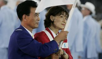 FILE - In this Friday Aug. 13, 2004 file photo, South Korean volleyball player Ku Min-jing, right, and North Korean former basketball player Kim Seong Ho carry a unification flag symbolizing one Korea during the Opening Ceremony of the 2004 Olympic Games in Athens. South Korean organizers for this year's Asian Games said Tuesday they've asked the International Olympic Committee to help bring North Korea to the quadrennial sports events. (AP Photo/Eric Risberg)