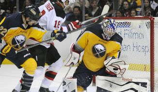 Buffalo Sabres left winger Johan Larsson (22) battles with New Jersey Devils right winger Steve Bernier (18) as Sabres goaltender Nathan Lieuwen (50) makes a save during the second period of an NHL hockey game in Buffalo, N.Y., Tuesday, April 1, 2014. (AP Photo/Gary Wiepert)