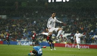 Real's Cristiano Ronaldo, top, in action with Rayo's goalkeeper Ruben, left, during a Spanish La Liga soccer match between Real Madrid and Rayo Vallecano at the Santiago Bernabeu stadium in Madrid, Spain, Saturday, March 29, 2014. (AP Photo/Andres Kudacki)