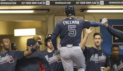 Atlanta Braves' Freddie Freeman is greeted by teammates after hitting a solo home run off of Milwaukee Brewers' Zach Duke during the eighth inning of a baseball game Tuesday, April 1, 2014, in Milwaukee. (AP Photo/Tom Lynn)