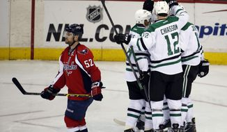 The Dallas Stars celebrate a goal by center Dustin Jeffrey (11) with Washington Capitals defenseman Mike Green (52) passing nearby, in the third period of an NHL hockey game, Tuesday, April 1, 2014, in Washington. The Stars won 5-0. (AP Photo/Alex Brandon)
