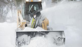 A plow clears snow from a sidewalk, Tuesday, April 1, 2014, in Fergus Falls, Minn. A spring blizzard that dumped heavy amounts of snow in parts of the Upper Midwest on Monday. (AP Photo/The Fergus Falls Daily Journal, Rian Bosse)