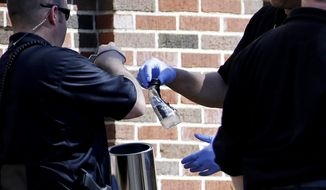 A police officer holds a bottle to collect as evidence while investigating a suspected incendiary device that was found outside Alonzo Crim Open Campus High School, Tuesday, April 1, 2014, in Atlanta. Atlanta Fire Rescue spokeswoman Janet Ward says authorities were called to a small fire outside the school Tuesday afternoon. Ward says the fire was extinguished before firefighters arrived and arson investigators are also on the scene. Local media outlets reported that authorities recovered a plastic bottle containing an undisclosed liquid. No injuries have been reported. (AP Photo/David Goldman)