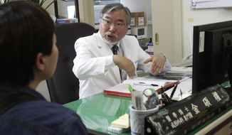 ** FILE ** In this March 18, 2014, photo, Dr. Kim Seok-Kwun, 61, talks with an unidentified patient at Dong-A University Hospital in Busan, South Korea. (AP Photo/Ahn Young-joon)