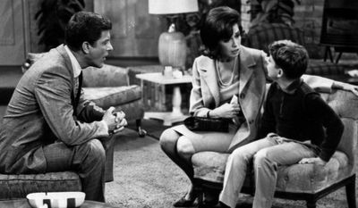 """FILE - In this 1965 file photo, from left, Dick Van Dyke, as Rob Petrie, and Mary Tyler Moore, as Laura Petrie, talk to Larry Matthews, who plays their son, Ritchie, on """"The Dick Van Dyke Show."""" Moore is being spotlighted in a new DVD collection called """"The Dick Van Dyke Show: Classic Mary Tyler Moore Episodes."""" The set gathers 20 episodes that dwell on the home life of Rob and Laura Petrie, putting the comic radiance of Moore on full display. (AP Photo/File)"""