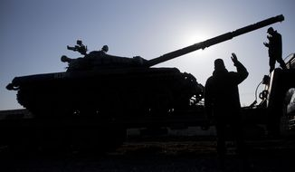 Russian officers gesticulate to the driver of Russian tank T-72B at the Ostryakovo railway station not far from Simferopol, Crimea, Monday, March 31, 2014. Russian tanks T-72B will be stationed on former Ukrainian military bases. (AP Photo/Pavel Golovkin)