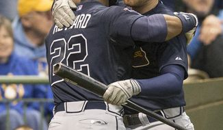 Atlanta Braves' Jason Heyward is greeted by teammate Freddie Freeman after Heyward hit a two run homer off of Milwaukee Brewers' Kyle Lohse during the fifth inning of a baseball game Tuesday, April 1, 2014, in Milwaukee. (AP Photo/Tom Lynn)