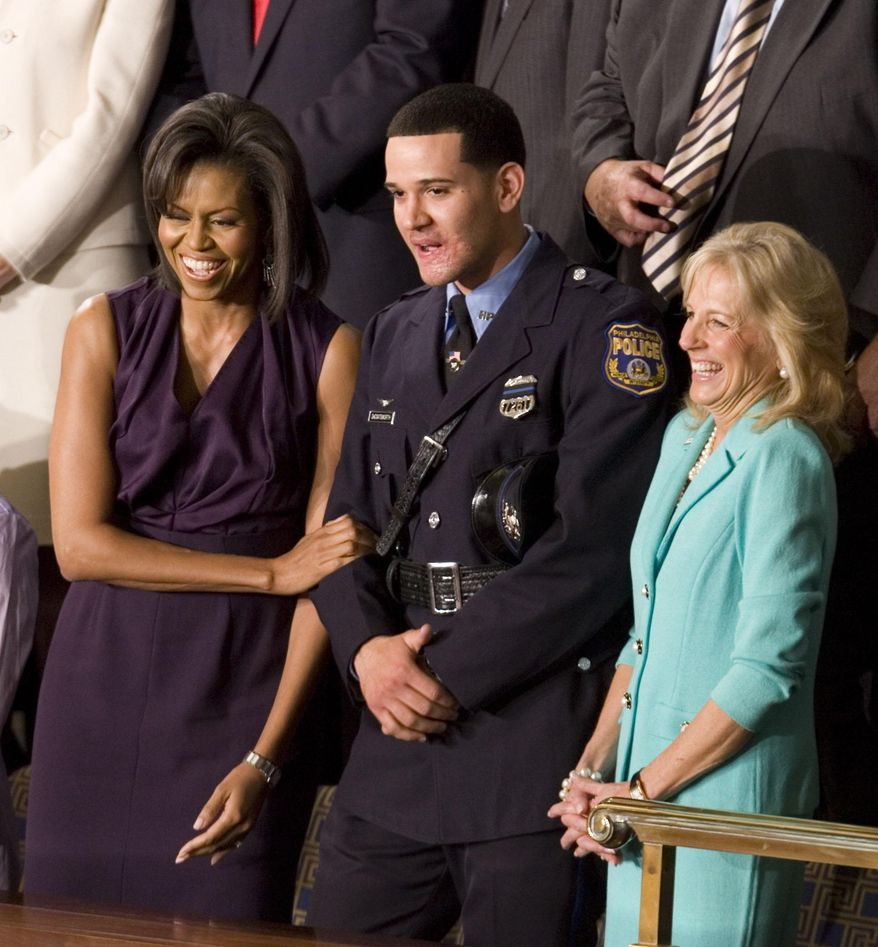 FILE - In this Tuesday, Feb. 24, 2009 file photo, first lady Michelle Obama and Jill Biden, wife of Vice President Joe Biden, stand with Philadelphia Police Officer Richard DeCoatsworth during President Barack Obama's address to a joint session of Congress in the House Chamber of the Capitol in Washington.  The former Philadelphia police officer who was hailed as a hero will stand trial on charges he raped two prostitutes at gunpoint. The November trial comes after the 28-year-old DeCoatsworth withdrew a plea to reduced charges Tuesday, April 1, 2014. (AP Photo/Evan Vucci, File)
