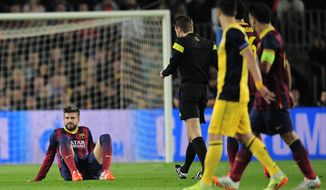 Barcelona's Gerard Pique, left sits on the pitch after getting injured during a first leg quarterfinal Champions League soccer match between Barcelona and Atletico Madrid at the Camp Nou stadium in Barcelona, Spain, Tuesday April 1, 2014. (AP Photo/Manu Fernandez)
