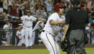 Arizona Diamondbacks' Miguel Montero, left, argues with umpire Tom Hallion, right, after Hallion initially called Montero out at home plate until he realized San Francisco Giants catcher Buster Posey dropped the ball during the fourth inning of an opening day baseball game, Monday, March 31, 2014, in Phoenix. (AP Photo/Ross D. Franklin)