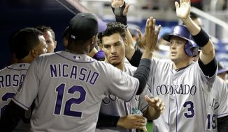 Colorado Rockies' Michael Cuddyer (3) is congratulated in the dugout after scoring on a double by Carlos Gonzalez in the eighth inning of a baseball game, Tuesday, April 1, 2014, in Miami. The Marlins defeated the Rockies 4-3. (AP Photo/Lynne Sladky)