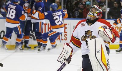 New York Islanders celebrate a goal by Matt Martin as Florida Panthers goalie Scott Clemmensen looks up during the second period of an NHL hockey game at Nassau Coliseum in Uniondale, N.Y., Tuesday, April 1, 2014. (AP Photo/Paul J. Bereswill)