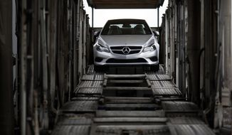 In this March 27, 2014 picture, a Mercedes-Benz vehicle sits inside a car-carrier before being hauled away for distribution from the company's Vehicle Processing Center in Baltimore. After sales slumped in January and February because of the brutal weather, automakers hope a rebound in March get them back on track to sell more than 16 million cars in the U.S. this year.  (AP Photo/Patrick Semansky)