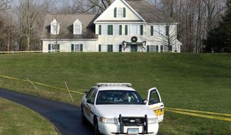 FILE - In this Dec. 18, 2012, file photo, a police cruiser sits in the driveway as crime scene tape surrounds the home of Nancy Lanza in Newtown, Conn. Nancy Lanza was killed there by her son Adam Lanza, before he forced his way into Sandy Hook Elementary School in Dec. 14, 2012 in Newtown, where he killed 26 children and adults. Some Newtown residents said in a survey released Monday, March 31, 2014, that they want the home torn down and the property turned into a park or nature preserve. (AP Photo/Jason DeCrow, File)