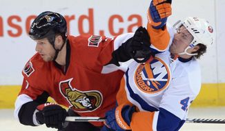 Ottawa Senators' Marc Methot pushes New York Islanders' Mike Halmo out of the way during the second period of an NHL hockey game in Ottawa, Ontario, on Wednesday, April 2, 2014. (AP Photo/The Canadian Press, Sean Kilpatrick)