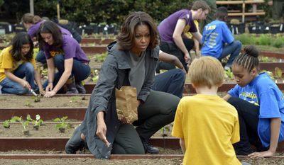 First lady Michelle Obama talks with Friendship Public Charter Elementary School student Dynasty Meade, right, and Bancroft Elementary School student Silas Stutz, second from right in yellow, as they plant Lincoln oats in the White House Kitchen Garden at the White House in Washington, Wednesday, April 2, 2014. (AP Photo/Susan Walsh)