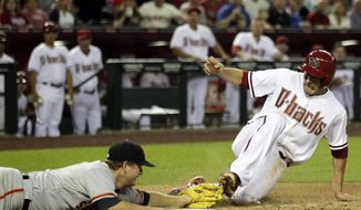 Arizona Diamondbacks center fielder A.J. Pollock (11) beats the tag from San Francisco Giants starting pitcher Matt Cain (18) in the fourth inning during a baseball game, Tuesday, April 1, 2014, in Phoenix. Pollock scored on a passed ball. (AP Photo/Rick Scuteri)