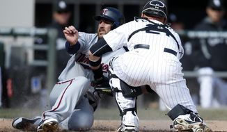 Chicago White Sox catcher Tyler Flowers tags out the Minnesota Twins' Trevor Plouffe at home plate during the seventh inning of an MLB American League baseball game on Wednesday, April 2, 2014, in Chicago. (AP Photo/Andrew A. Nelles)