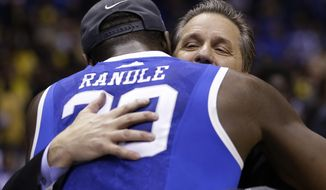Kentucky head coach John Calipari hugs Julius Randle after an NCAA Midwest Regional final college basketball tournament game against Michigan Sunday, March 30, 2014, in Indianapolis. Kentucky won 75-72 to advance to the Final Four.(AP Photo/David J. Phillip)
