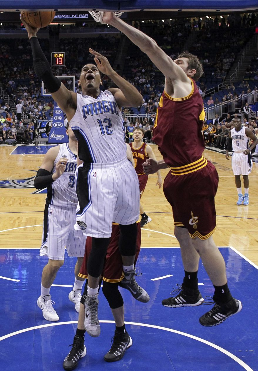 Orlando Magic's Tobias Harris (12) makes a shot around Cleveland Cavaliers' Tyler Zeller, right, during the first half of an NBA basketball game in Orlando, Fla., Wednesday, April 2, 2014. (AP Photo/John Raoux)