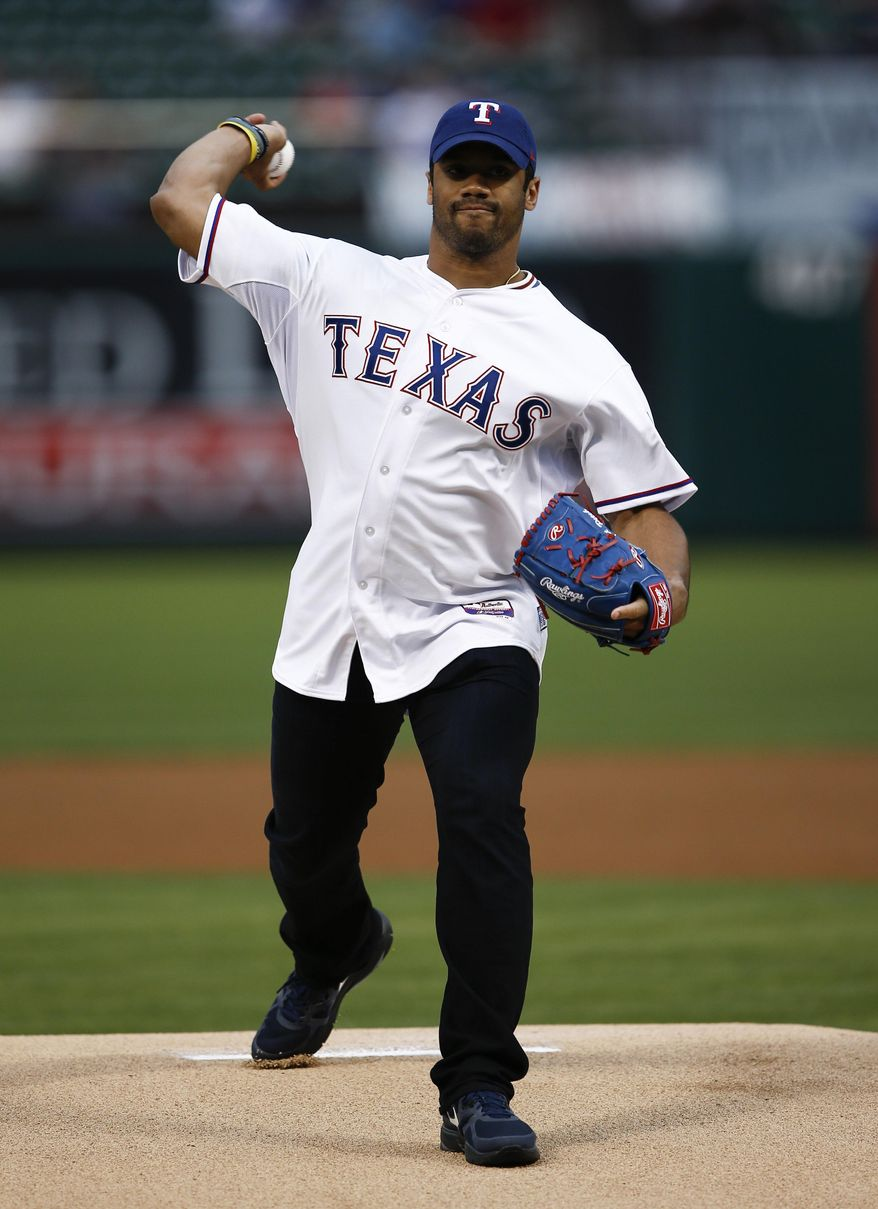 Seattle Seahawks quarterback Russell Wilson throws out the ceremonial first pitch before a baseball game between the Texas Rangers and the Philadelphia Phillies, Wednesday, April 2, 2014, in Arlington, Texas. (AP Photo/Jim Cowsert)
