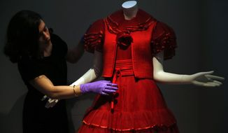 A V&A museum employee poses for the photographers with a 1977 red tulle evening dress by Valentino Couture at an exhibition entitled: 'The Glamour of Italian Fashion 1945-2014', at the V&A museum in London, Wednesday, April 2, 2014. The show, which according to the museum, is the first to examine Italy's rich and influential contribution to fashion from the end of the Second World War to the present, opens on April 5 to July 27, 2014. On display are around 120 ensembles and accessories by leading Italian fashion houses and the exhibition follows the story from the landmark catwalk shows in the 1950s to the impact of Hollywood films shot on location in Italy during the 1950s/60s where stars like Audrey Hepburn and Elizabeth Taylor became style ambassadors for Italian fashion. (AP Photo/Lefteris Pitarakis)