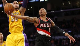 Portland Trail Blazers guard Damian Lillard, right, goes to the basket Los Angeles Lakers center Robert Sacre defends during the second half of an NBA basketball game in Los Angeles, Tuesday, April 1, 2014. (AP Photo/Danny Moloshok)