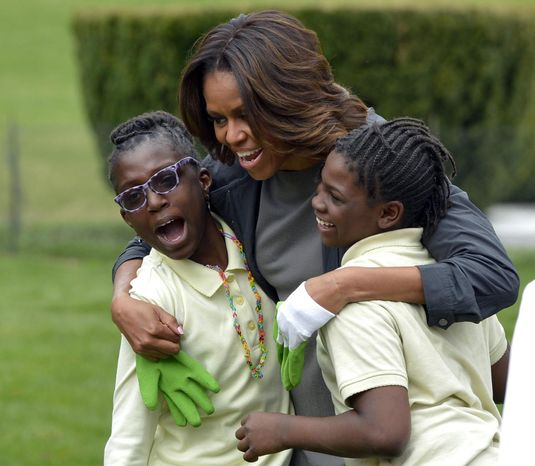 First lady Michelle Obama hugs two students as she arrives to plant the White House Kitchen Garden at the White House in Washington, Wednesday, April 2, 2014. (AP Photo/Susan Walsh)