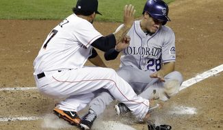 Colorado Rockies' Nolan Arenado (28) collides with Miami Marlins starting pitcher Henderson Alvarez, left, as he scores on a wild pitch in the fourth inning of a baseball game on Wednesday, April 2, 2014, in Miami.  (AP Photo/Lynne Sladky)