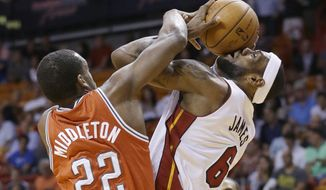 Miami Heat forward LeBron James (6) goes up to shoot against Milwaukee Bucks forward Khris Middleton (22) during the first half of an NBA basketball game on Wednesday, April 2, 2014, in Miami. (AP Photo/Wilfredo Lee)