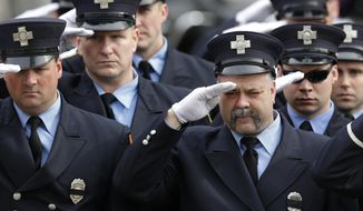 Firefighters salute as the funeral procession of Boston Fire Lt. Edward Walsh arrives outside the Church of Saint Patrick in Watertown, Mass., Wednesday, April 2, 2014. Walsh and Boston Firefighter Michael Kennedy died after being trapped while battling a fire in Boston. (AP Photo/Charles Krupa)