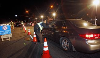 Police officers check drivers at a sobriety checkpoint in Escondido, Calif., on Dec. 16, 2011. (Associated Press)