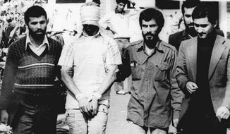 **FILE** In this Nov. 9, 1979, file photo, one of the hostages being held at the U.S. Embassy in Tehran is displayed to the crowd, blindfolded and with his hands bound, outside the embassy. Fifty-two of the hostages endured 444 days of captivity.  (AP Photo/File)