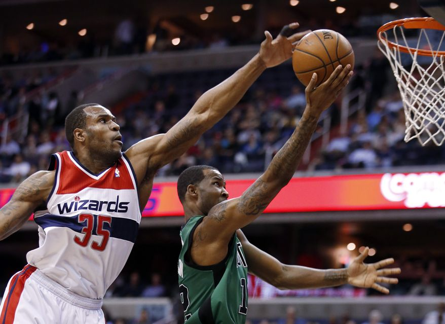 Washington Wizards forward Trevor Booker (35) blocks a shot by Boston Celtics forward Chris Johnson (12) during the first half of an NBA basketball game Wednesday, April 2, 2014, in Washington. (AP Photo/Alex Brandon)
